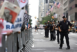 NYPD Officers line up along barricaded Anti-Trump protestors as they holds signs during a pro-migration rally near Trump Tower during President Donald Trump's first stay in New York City since taking office, New York, NY, on August 15, 2017. (Photo by Anthony Behar)
