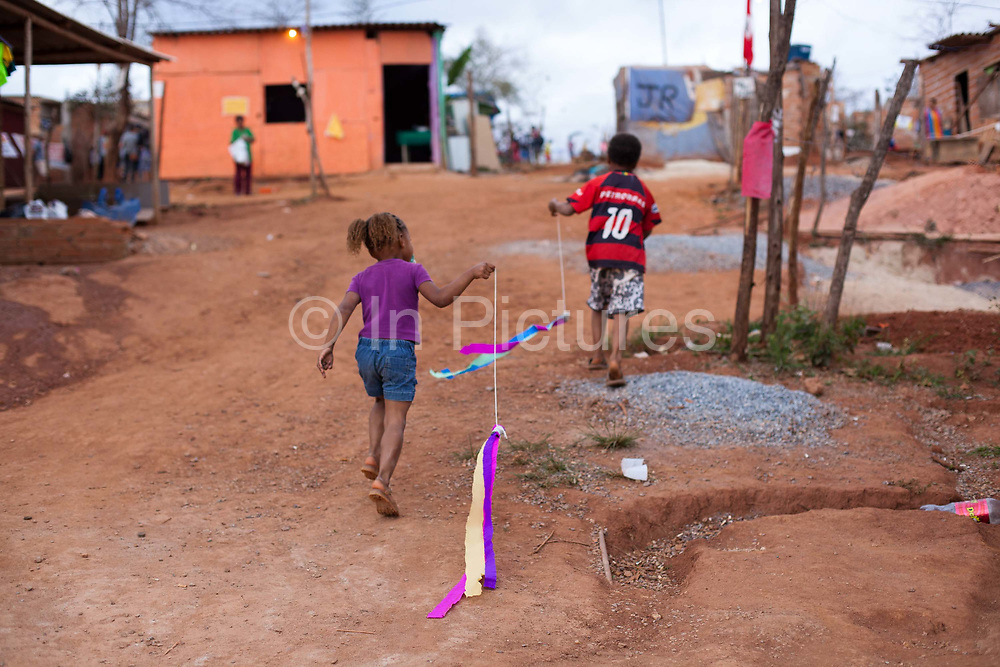 Two children with kites walk up the hill. Isidoro occupation in Belo Horizonte, Minas Gerais in a large  amount of land that was occupied by the MLB, a Brazilian workers social movement, it faced eviction in July / August 2014. (photo by Phil Clarke Hill/In Pictures via Getty Images)