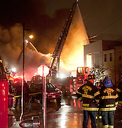 Baltimore City Firefighters and HAZMAT personnel work to contain the fire in this Canton warehouse that contains unknown chemicals, Monday, April 22, 2013