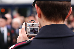 © under license to London News Pictures. 14/11/2010. Uniformed onlooker takes a picture of the veterans marching out of Centenary Square on Remeberance Sunday. Photo credit should read Jason Patel/London News Pictures