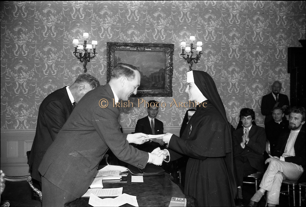 """23/05/1966<br /> 05/23/1966<br /> 23 May 1966<br /> 1916 Art prizes presented at Iveagh House. Prizes for literature, music and art offered by the 1916 Golden Jubilee Commemoration Committee were presented by the Minister for Education Mr. George Colley T.D. at a ceremony at Iveagh House, Dublin. Picture shows Sister Máire Fionntan, Clochar na Toirbhirte, Cill Coca, Co. Kildare receiving her prize of £100 for an original poem in Irish """"An Gineadh"""", from George Colley, T.D. Minister for Education."""