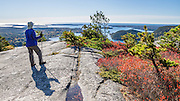 Hike Acadia Mountain Trail for good views of Somes Sound and typically peak fall colors in the second week of October, in Acadia National Park, Bar Harbor, Mount Desert Island, Maine, USA. Hike granite peaks and enjoy Atlantic coastal scenery. Originally created as Lafayette National Park in 1919, the oldest National Park east of the Mississippi River, it was renamed Acadia in 1929. During the last glacial maximum 21,000 years ago, glaciers measuring up to 9,000 feet thick cut into granite ridges, sculpting the fjord-like Somes Sound.