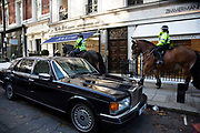 Police horses on the pavement pass a Rolls Royce car for the Global Climate Strike organised by UK Student Climate Network on 29th November 2019 in London, United Kingdom. The School strike for climate, also known as Fridays for Future, FFF, Youth for Climate and Youth Strike 4 Climate, is an international movement of school students who are deciding not to attend classes and instead take part in demonstrations to demand action to prevent further global warming and climate change. UK Student Climate Network is calling on everyone - adults, workers, community groups, trade unionists, nurses, teachers, steel workers, car manufacturers, waiters and everyone else in between to join them in a global general climate strike. This protest will join people all around the world in a massive day of climate action.