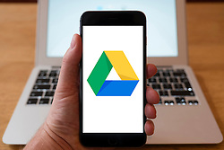 Using iPhone smartphone to display logo of Google Drive cloud based storage service