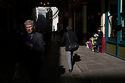 Reflected light in the City of London, England, United Kingdom. Flower seller in Leadenhall Market.