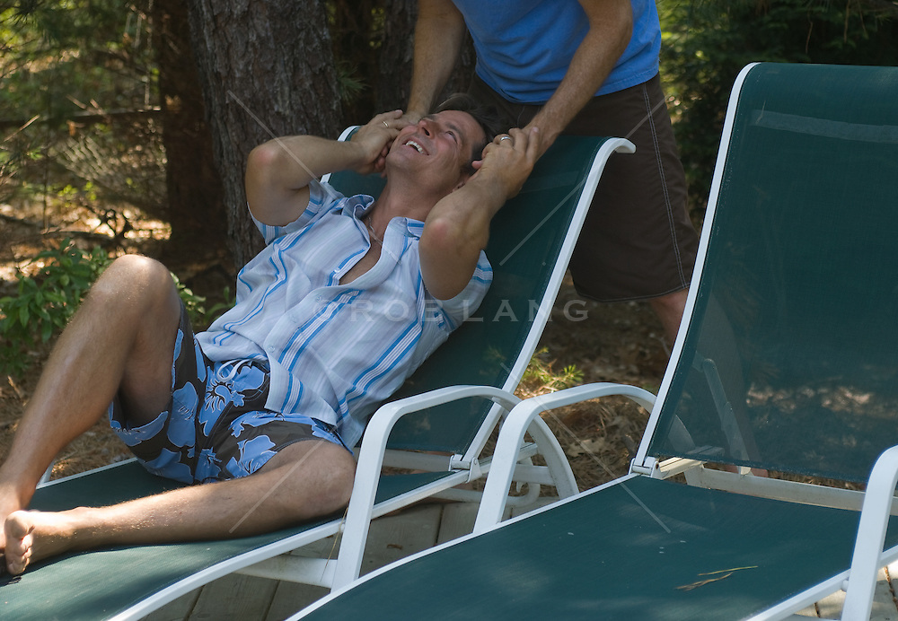 Man relaxing on a lounge chair looking up smiling holding a man's hands