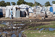 Man walking by open water next to shelters in a tent city in Port-au-Prince. The lack of clean water makes Haiti ripe for the spread of cholera.  Since the earthquake on January 12, 2010, thousands still live in tent cities that lack sanitation.