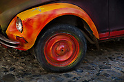 Brightly painted orange & yellow Citroen 2CV French car wheel on cobbled street.