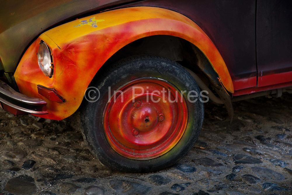 Brightly painted orange & yellow Citroen 2CV French car wheel on cobbled street.