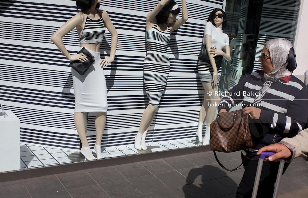 Woman shopper walks past stripe-themed shop window display.