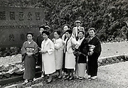 Japanese tourist group posing at a sign of a national park in Japan 1960s