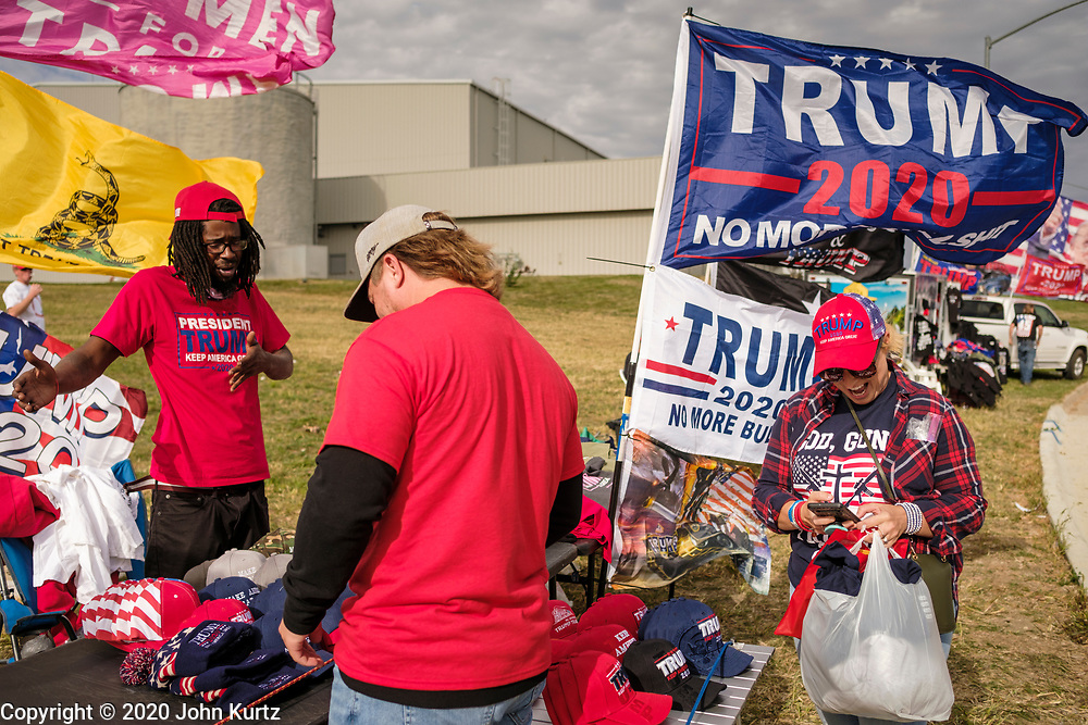 14 OCTOBER 2020 - DES MOINES, IOWA: People shop for Donald Trump merchandise before a Trump reelection rally in Des Moines. About10,000 people were expected at the Des Moines International Airport for a campaign rally supporting the reelection of President Donald Trump. Trump spoke at the rally, despite testing positive for COVID-19 less than three weeks ago. The rally did not meet the CDC guidelines for a safe gathering in the time of Coronavirus and violated Iowa's health emergency declarations barring gatherings of more than 25 people. This week Iowa exceeded 101,000 cases of COVID-19 and a surge in hospitalizations for COVID-19.        PHOTO BY JACK KURTZ