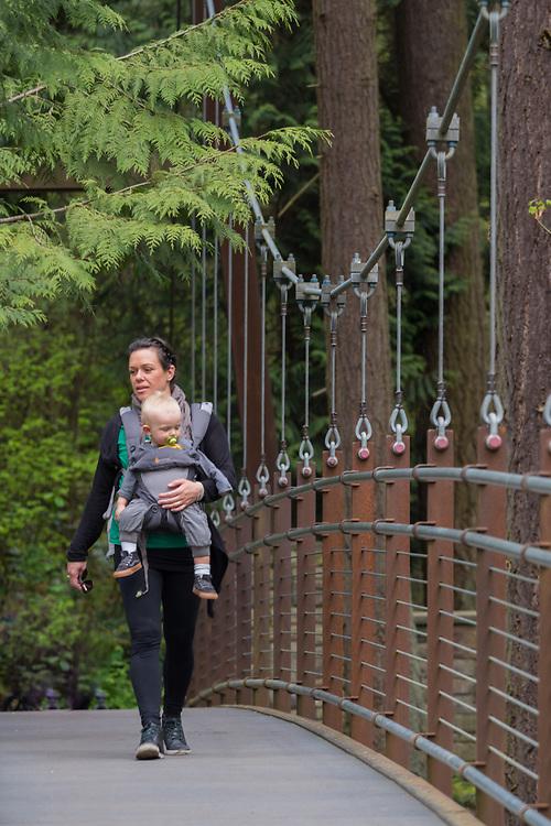 United States, Washington, Bellevue, woman with baby crossing suspension bridge (Ravine Experience) at Bellevue Botanical Garden