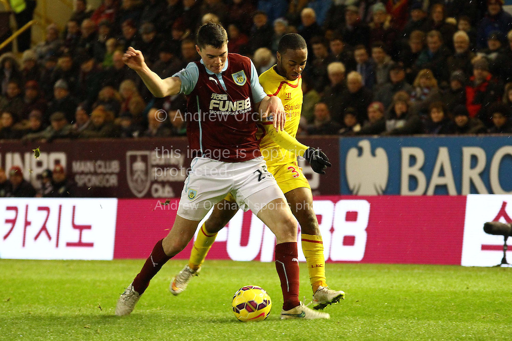 Michael Keane of Burnley shields the ball from Raheem Sterling of Liverpool. Barclays Premier league match, Burnley v Liverpool at Turf Moor in Burnley, Lancs on Boxing Day, Friday 26th December 2014.<br /> pic by Chris Stading, Andrew Orchard sports photography.