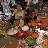 A woman makes juice in her shop in an outdoor market in upper Belem, a crowded neighborhood in Iquitos, Peru.