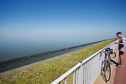 Fietsers rijden over de Afsluitdijk. In 1932 werd de opening tussen de Waddenzee (links) en de toenmalige Zuiderzee gesloten. Nu is het een belangrijke verkeersader tussen Friesland en Noord-Holland en scheidt het de Waddenzee met het IJsselmeer.<br /> <br /> Cyclists are riding on the Afsluitdijk. In 1932, the gap between the Wadden Sea and the former Zuiderzee closed by the Afsluitdijk. Now it is a major thoroughfare between Friesland and North Holland and it separates the Wadden Sea from the IJsselmeer.