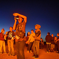 Lavin Skeets shields his face and videos the action as he and his fellow Miyamura High School students gather around the annual homecoming bonfire Thursday at Miyamura High School. Miyamura will face off with the Grants Pirates for their homecoming game Friday at Public School Stadium.