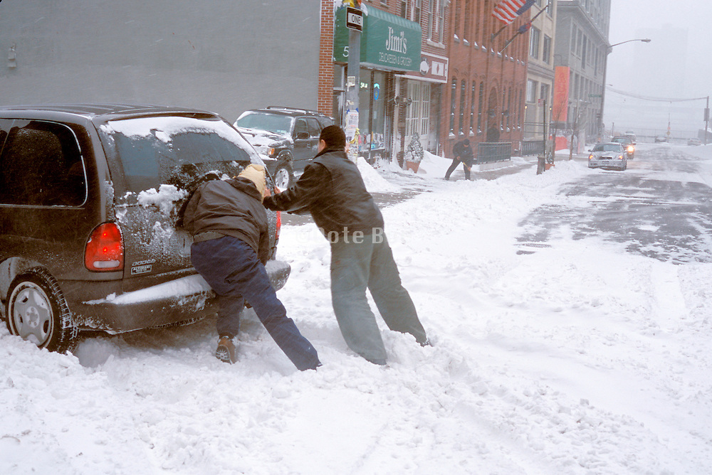 two people pushing a car stuck in the snow