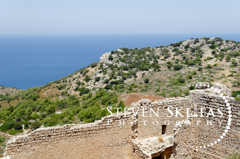 Rhodes. Greece. The blue waters of the Aegean Sea and the fortifications of Kritinia Castle (Castle of Castello) on the west coast of Rhodes Island. Dating from 16th century the medieval strategic fortress was built by the Knights of St John and once boasted several coats of arms of several Grand Masters. It is surrounded by olive groves and pines wood and offers spectacular views of the Aegean Sea and the Wild West Coast of Rhodes Island. The island of Rhodes is the largest of the Dodecanese Island group and one of the most popular Greek Islands.
