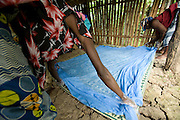 Women lay a treated mosquito net to dry as they demonstrate the technique for fellow villagers in the village of Issaba, Benin on Friday September 14, 2007.