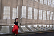 In the week that many more Londoners returned to their office workplaces after the Covid pandemic, a woman City worker walks past sun reflections on the walls of the Bank of England in the City of London, the capital's financial district, on 8th September 2021, in London, England.