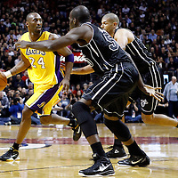 19 January 2012: Los Angeles Lakers shooting guard Kobe Bryant (24) looks for a teammate as Miami Heat center Joel Anthony (50) and Miami Heat small forward Shane Battier (31) defend during the Miami Heat 98-87 victory over the Los Angeles Lakers at the AmericanAirlines Arena, Miami, Florida, USA.