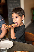 Avo Khan enjoys a slice of wood-fired pizza at Delancey in the Ballard neighborhood of Seattle, Wa.