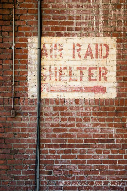 Air raid shelter sign painted on a brick wall at Winehaven, a dilapidated California winery and former Naval fuel depot at Point Molate in Richmond, California.