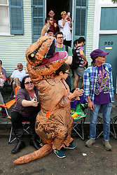 31 January 2016. New Orleans, Louisiana.<br /> Mardi Gras Dog Parade. Kid in a dinosaur costume at the Mystic Krewe of Barkus as the parade winds its way around the French Quarter with dogs and their owners dressed up for this year's theme, 'From the Doghouse to the Whitehouse.' <br /> Photo©; Charlie Varley/varleypix.com