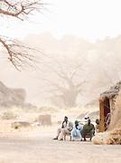 Men of the Nuba tribe sit outside a mud hut in the village of Nyaro, Kordofan region, Sudan