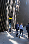 Businessmen walk past a map of the City of London which is positioned beneath corporate office architecture, in the capital's financial district, on 24th September 2021, in London, England.