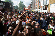On Kensal Road a group of young men energetically dance together, crashing into one another as the bass and volume brings the atmosphere to a fervour on Monday 28th August 2016 at the 50th Notting Hill Carnival in West London. A celebration of West Indian / Caribbean culture and Europes largest street party, festival and parade. Revellers come in their hundreds of thousands to have fun, dance, drink and let go in the brilliant atmosphere. It is led by members of the West Indian / Caribbean community, particularly the Trinidadian and Tobagonian British population, many of whom have lived in the area since the 1950s. The carnival has attracted up to 2 million people in the past and centres around a parade of floats, dancers and sound systems.