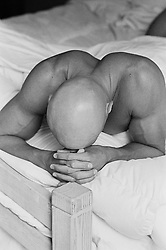 Bald man lying in bed with his head on his hands, b&w