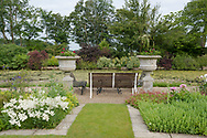 Stone urns and a seating area surrounded by Astilbe in the formal garden next to the moat at Hindringham Hall, Hindringham, Norfolk, UK
