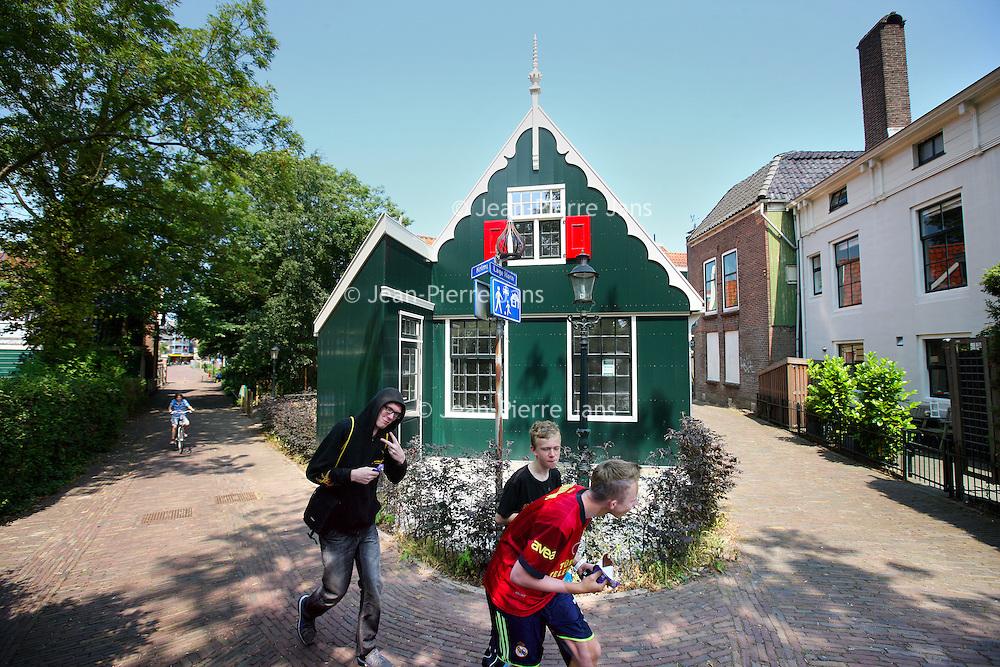 Nederland, Zaandam , 5 juli 2013.<br /> Wandeling door de binnenstad van Zaandam.<br /> Starten bij De Werf aan de Oostzijde. Daarvandaan kun je lopen op een soort boulevard tussen de flats en het water. De eerste stop is De Fabriek, filmhuis en eetcafé met terras aan de Zaan met uitzicht op de sluis. Daarna de sluis zelf.<br /> Dan langs het winkelgebied richting de Koekfabriek: Het oude Verkade pand dat is verbouwd en waar nu de bieb en sportschool en restaurant etc. in zitten.<br /> (Dat is aan de overkant van het startpunt) en misschien nog de Zwaardemaker meepakken aan de Oostzijde. Dat is een oud pakhuis die Rochdale enige jaren geleden heeft verbouwt tot appartementen met een stukje Nieuwbouw.<br /> Ook doen: het Russische buurtje vlakbij de Zaan. Dit jaar staat Rusland in de schijnwerpers en Zaandam heeft een speciale band met Rusland, vanwege het Czaar Peterhuisje en de Russische buurt. <br /> Op de foto: het straatje Lage Horn met typische Zaanse huisjes.<br /> Foto:Jean-Pierre Jans