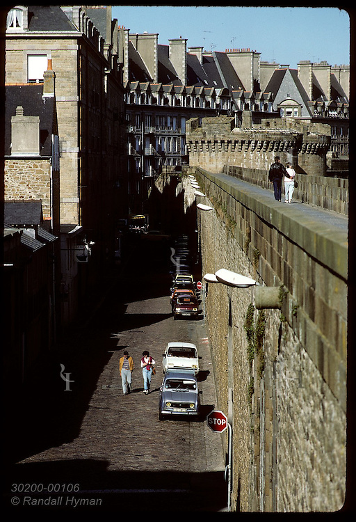 Couple walks along the battlements of Saint Malo as another couple walks on the street below France