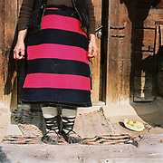 A peasant woman wearing a striped apron (zadie) made from a single width of woven wool with horizontal pink and black stripes and traditional footwear (opinci) worn with felt foot wraps (obiele), Botiza, Maramures, Romania. Traditionally subsistence farmers In Maramures raise their own sheep to provide wool for knitting and weaving clothing.