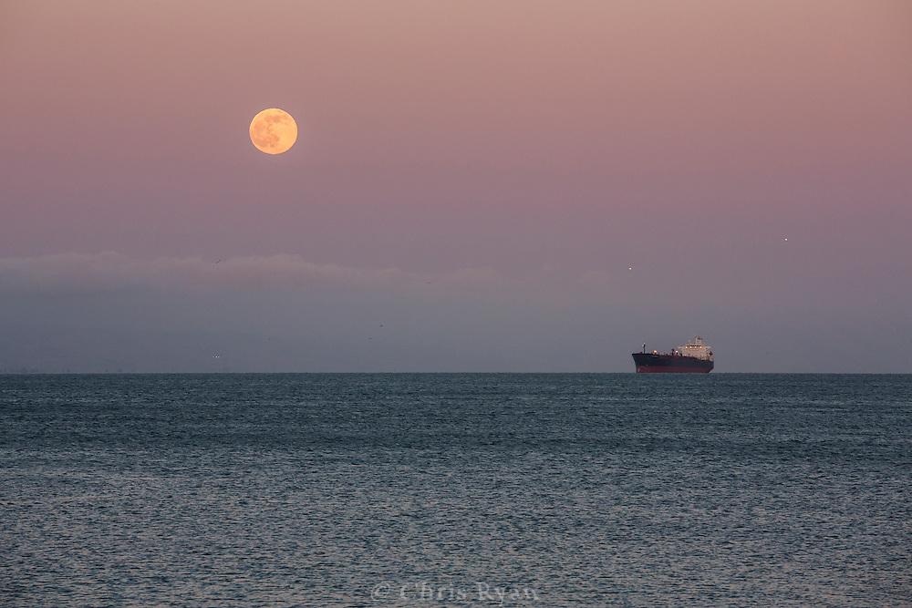 Full moon at dusk over tanker ship and San Francisco Bay, California
