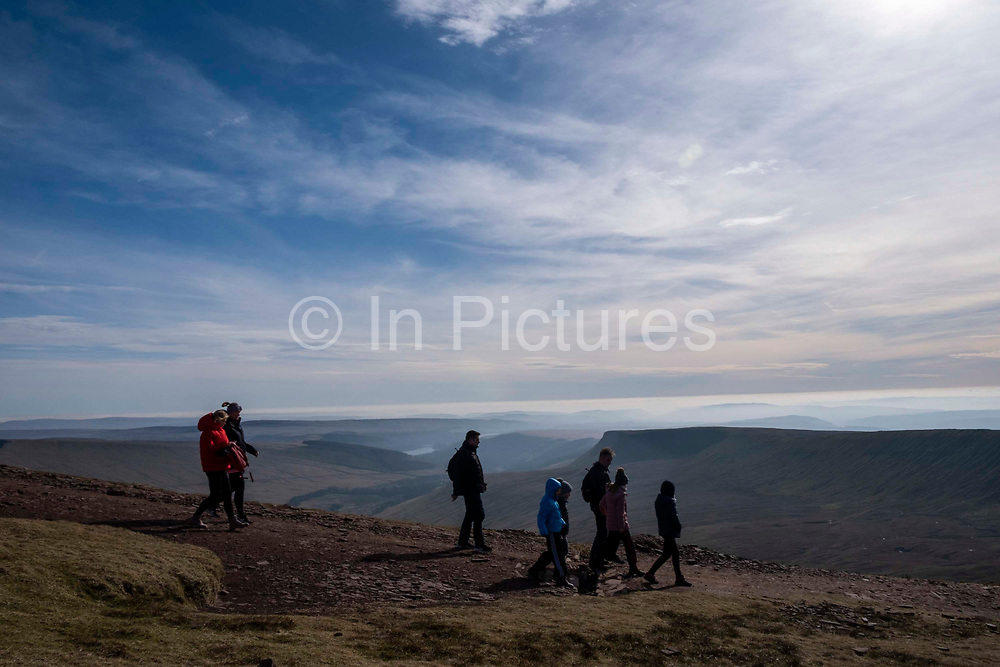 A group of adults and children walk along a dirt path descending from the summit of Pen Y Fan mountain in Brecon Beacons National Park, Wales, Powys, United Kingdom.  Pen Y Fan is the highest point in the Brecon Beacons hill and mountain range in South Wales. The National Park was established in 1957 due to the spectacular landscape which is rich in natural beauty and is run by the National Trust.