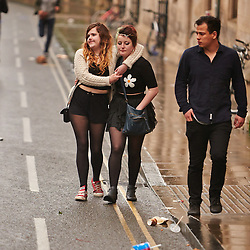© Licensed to London News Pictures.  01/05/2014. OXFORD, UK. Students walk down High St in Oxford on May Morning. Each year at 6am the Magdalen College Choir performs the Hymnus Eucharisticus, from the top of Magdalen Tower, a tradition dating back over 500 years. Around 6,000 students and local residents, some of who have stayed up all night, gather in the street below to listen. Morris dancers then perform around the city. After a number of injuries in previous years a heavy security presence stopped anyone from jumping from the bridge into the Cherwell river. Photo credit: Cliff Hide/LNP