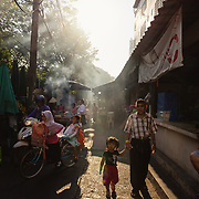 Dramatic afternoon light in a narrow alley in Thon Buri where locals cook street food