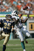 Miami Dolphins tight end Randy McMichael bobbles a pass before making the catch as St Louis Rams defensive back Aneas Williams defends as the Dolphins led the Rams 14-7 at halftime on October 24, 2004 at Pro Player Stadium in Miami, Florida.