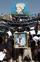 KABUL,AFGHANISTAN - SEPT. 9: Afghan women hold portraits of Ahmad Shah Massoud during a ceremony in Kabul Sports Stadium, September 9, 2002  to comemerate the anniversary of his death. (Photo by Ami Vitale/Getty Images)