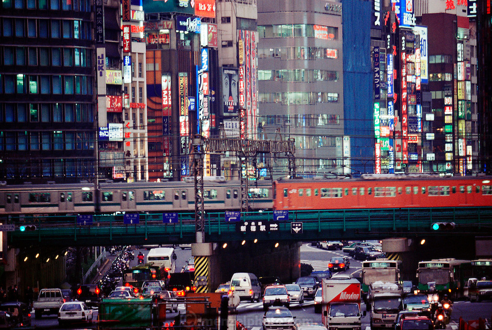 Subway trains cross an overpass over rush hour evening traffic in the Shinjuku area of Tokyo, Japan.