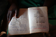"""Gabriel Owino, 10, looks over his science notebook during a lesson at attends Rabango Primary School in Western Kenya. Gabriel was 2 when he lost his mother to complications from AIDS a year after his father passed away from the same disease. The oldest brother Abraham, 16, was 7 when his mother died. He has been the head of the family ever since. He dropped out of school to support his four younger brothers and earns a living by giving people rides on a rented """"bora-bora"""" (moped).  The Owino brothers receive support from The Child Behind Project, which assists Orphans and Vulnerable Children (OVC) in the area. Sara A. Fajardo/Catholic Relief Services"""
