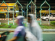 18 JUNE 2015 - PATTANI, PATTANI, THAILAND: Women on a motorcycle pass the Ramadan light display near the Pattani Central Mosque after Ramadan services. Thousands of people come to Pattani Central Mosque in Pattani, Thailand, to mark the first night of Ramadan. Ramadan is the ninth month of the Islamic calendar, and is observed by Muslims worldwide as a month of fasting to commemorate the first revelation of the Quran to Muhammad according to Islamic belief. This annual observance is regarded as one of the Five Pillars of Islam. Islam is the second largest religion in Thailand. Pattani, along with Narathiwat and Yala provinces, all on the Malaysian border, have a Muslim majority.     PHOTO BY JACK KURTZ