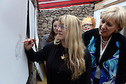 26-7-2015: Weather Humphreys?.....  Minister for Arts, Heritage and the Gaeltacht Heather Humphreys is sheltered from the driving wind and rain by Noelle Campbell-Sharpe during their visit to the Cill Rialaigh Famine Village in South Kerry on Sunday. Minister Humphreys also visited Ballinskelligs overlooking the Skellig Rocks where filming of the next episode of Star Wars is expected to begin this September.<br /> Picture by Don MacMonagle