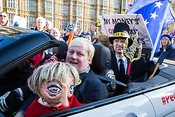 London, UK. 14th February, 2019. Boris Johnson lookalike Drew Galdron, also known as Faux BoJo, and a man disguised as Jacob Rees-Mogg are accompanied by a Theresa May puppet as they join anti-Brexit activists protesting outside the Houses of Parliament in Westminster.