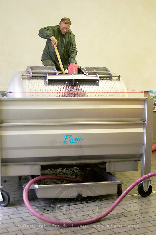 Domaine Haut-Lirou in St Jean de Cuculles. Pic St Loup. Languedoc. Wine press. Winery worker filling the press. France. Europe.