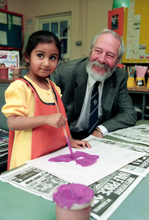 Older teacher with young Asian girl  in art class at primary school,